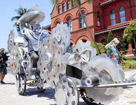 """Steve King rolls past the Custom House Museum with his pedal-and-belt-driven creation """"Time Chaser.""""  Following in pioneering folk artist Stanley Papio's footsteps, King used recycled materials combining wood, metal, bike parts, and """"bits and bobs"""" to make his award-winning gear-and-cogs-inspired design, one of more than thirty kinetic creations that participated in the rolling cavalcade held in honor of the late welder-turned artist. The zany spectacle of creative whimsy and kinetic savvy was supported in part by a prestigious grant awarded to the Society by the Knight Arts Challenge People's Choice Award, a competition that rewards the best and most innovative ideas for the arts. A permanent exhibit celebrating Papio's work is now open at Fort East Martello Museum in Key West, and preparations are already underway for next year's kinetic festivities.  Visit KWAHS.ORG for more information."""